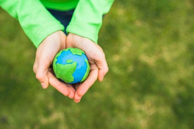 Vista de ángulo alto de las manos de una niña sosteniendo un globo de arcilla falso Foto gratis