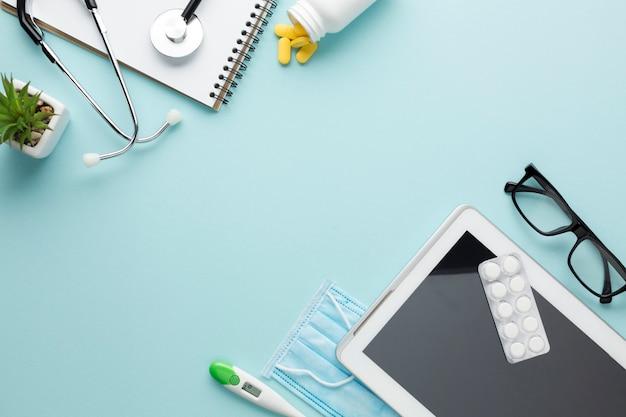 Vista de ángulo alto de mesa con medicina; tableta digital y accesorios médicos Foto gratis