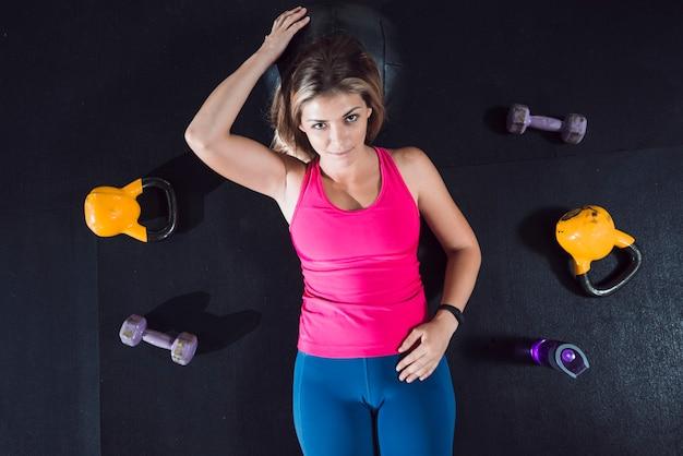 Vista de ángulo alto de la mujer en forma relajante en el piso cerca de equipos de ejercicio Foto gratis