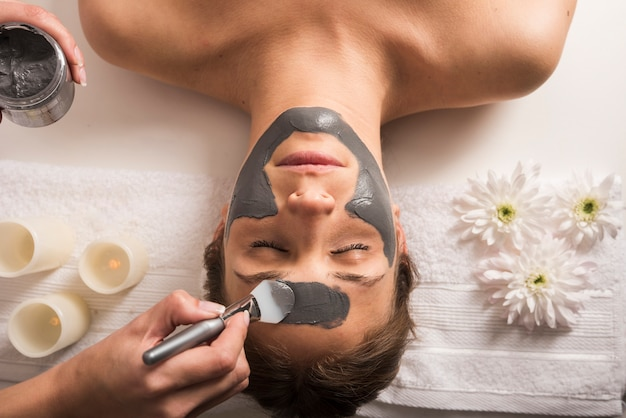 Vista de ángulo alto de una mujer que recibe máscara facial en el salón de belleza Foto gratis