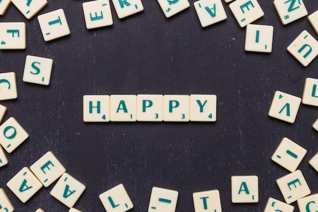 Vista de ángulo alto de la palabra feliz con letras scrabble Foto gratis
