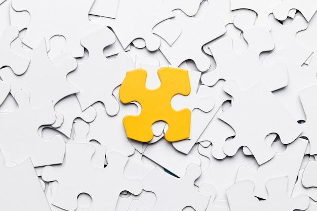 Vista de ángulo alto de una pieza de rompecabezas amarilla sobre piezas de un rompecabezas blanco Foto gratis