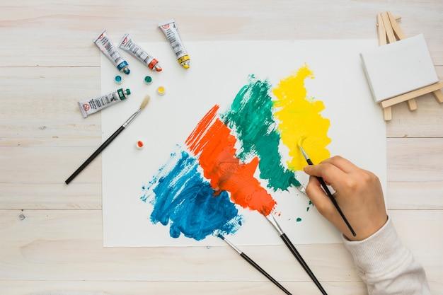Vista de ángulo alto de pintura de mano humana sobre papel blanco con pincelada colorida Foto gratis