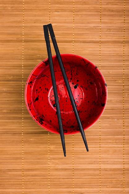 Vista de ángulo alto de un recipiente vacío con palillo negro sobre mantel Foto gratis