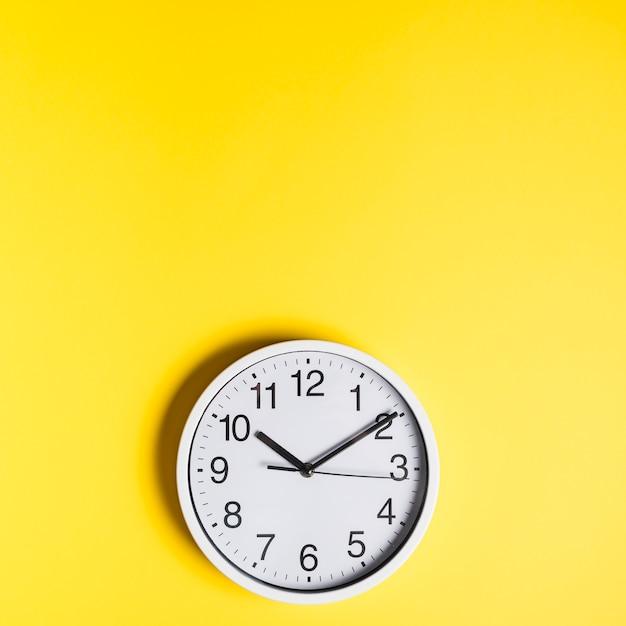 Vista de ángulo alto del reloj de pared sobre fondo amarillo Foto Premium