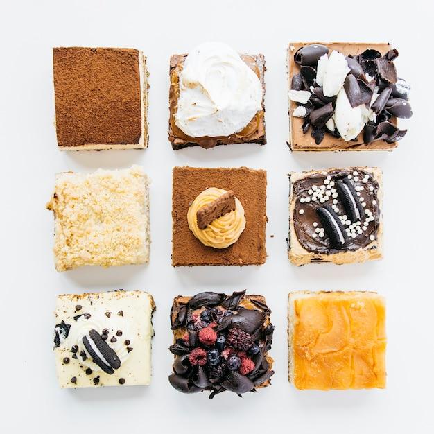 Vista de ángulo alto de varios pasteles deliciosos sobre fondo blanco Foto gratis
