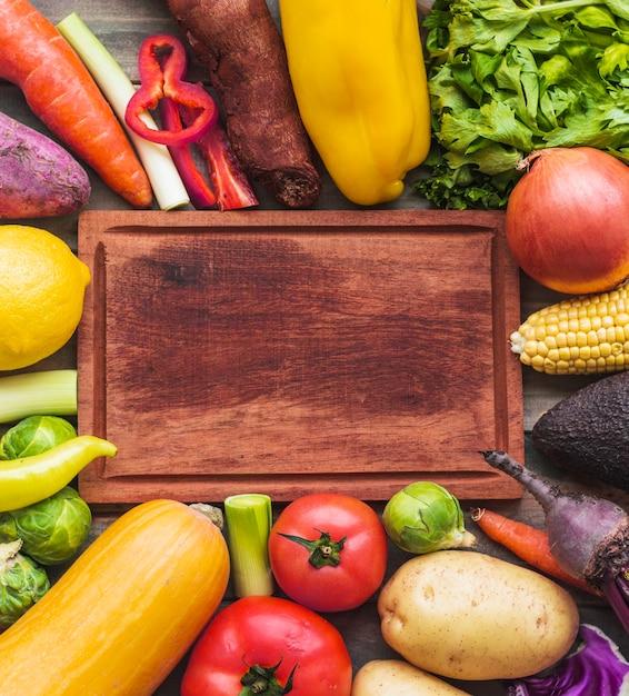 Vista de ángulo alto de verduras crudas que rodean tabla de cortar de madera Foto gratis