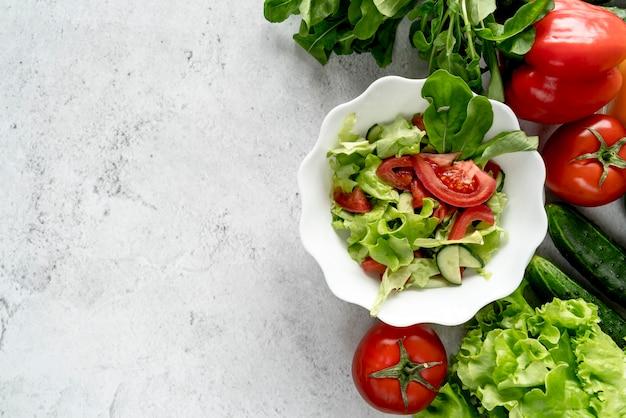 Vista de ángulo alto de verduras enteras con tazón de ensalada sobre fondo texturizado Foto gratis