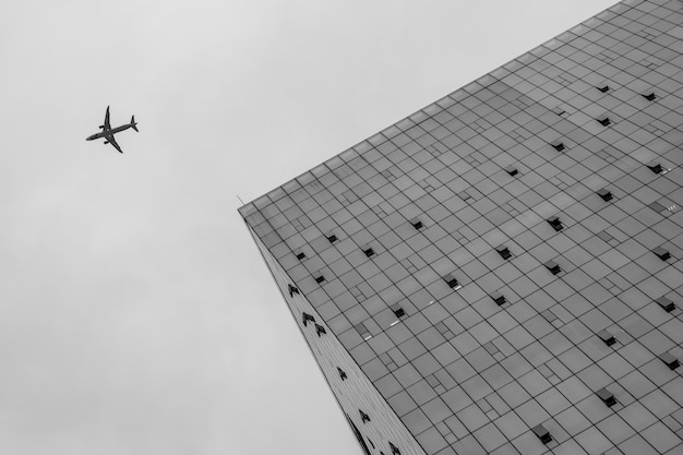 Vista de ángulo bajo a un edificio y un avión volando cerca de él en el cielo Foto gratis