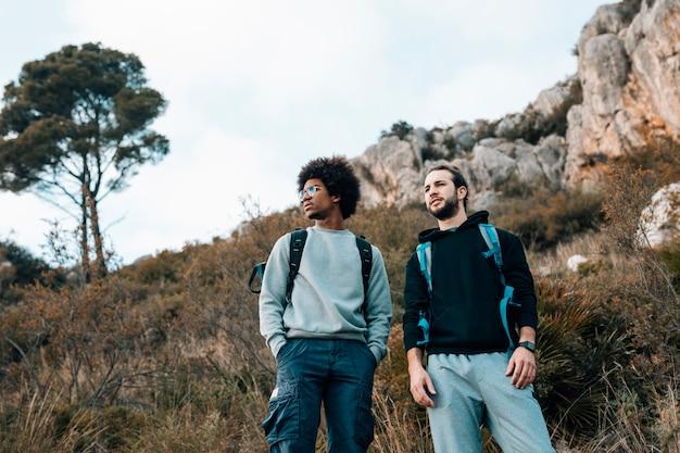 Vista de ángulo bajo de excursionistas multiétnicos masculinos Foto gratis