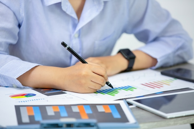 Vista de ángulo lateral de gente de negocios escribiendo sobre papeleo en la mesa Foto Premium