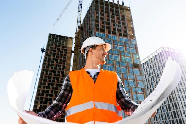 Vista de ángulo bajo de tiro medio del ingeniero de la construcción con planes Foto gratis