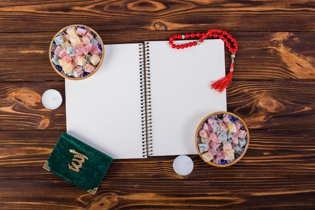 Una vista desde arriba del cuaderno en espiral con tazones lukum encantadores; cuentas de oración kuran y rojo en el escritorio de madera Foto gratis