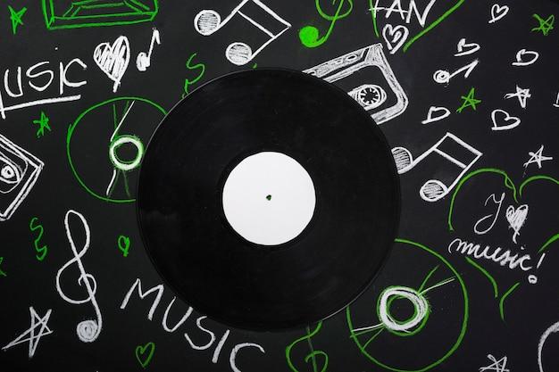 Una vista desde arriba del disco de vinilo sobre la pizarra con notas musicales dibujadas Foto gratis