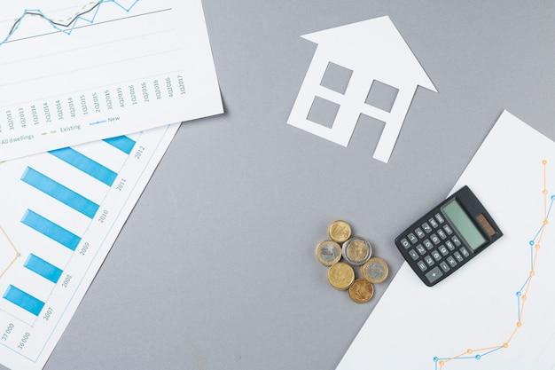 Vista de arriba del escritorio de negocios con monedas apiladas; calculadora; recorte de casa y gráfico Foto gratis