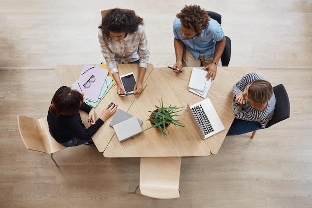 Vista desde arriba del grupo de jóvenes emprendedores profesionales sentados a la mesa en el espacio de coworking, discutiendo las ganancias del último proyecto de equipo, usando una computadora portátil, tableta digital y teléfono inteligente. Foto gratis