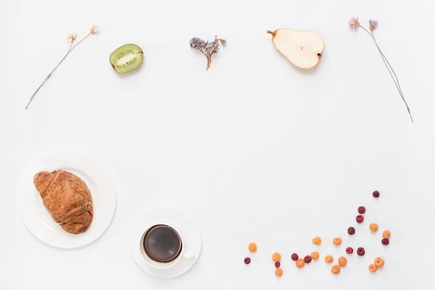 Una vista desde arriba del kiwi de café croissant a la mitad; peras; flor seca y frambuesas sobre fondo blanco Foto gratis