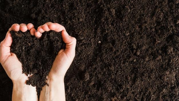 Una vista desde arriba de la mano de la mujer sosteniendo el suelo en forma de corazón Foto gratis