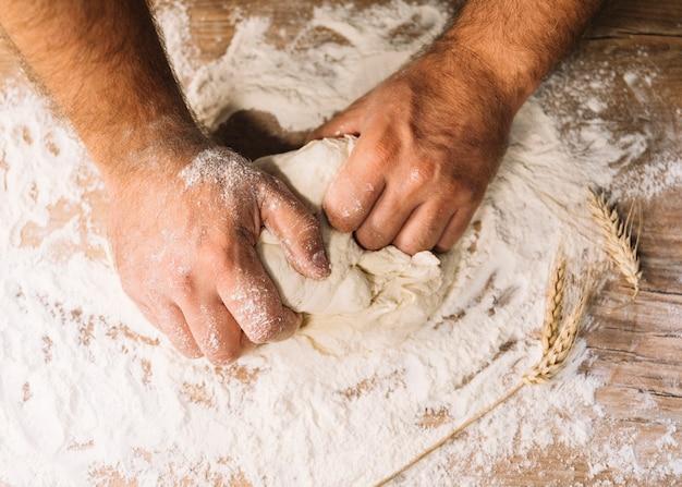 Una vista desde arriba de la mano del panadero amasando con harina de trigo en la mesa Foto gratis