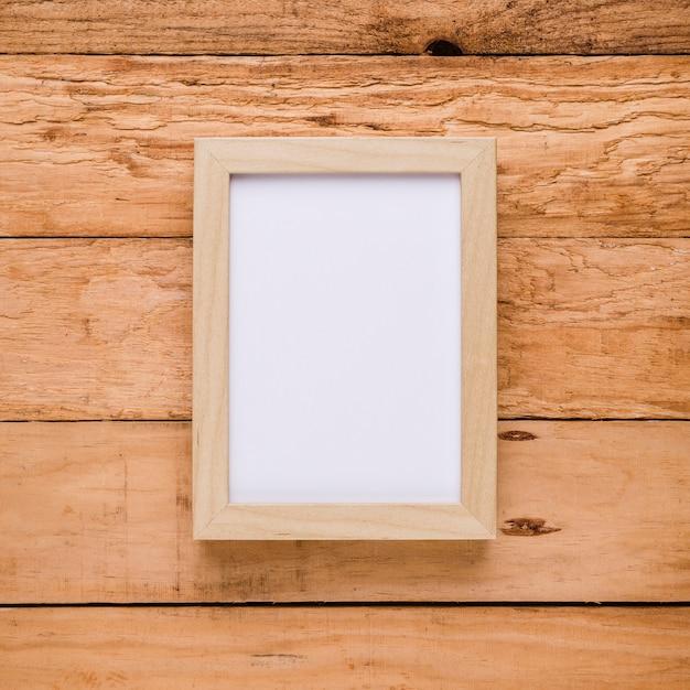 Vista de arriba del marco de imagen vacío sobre escritorio texturizado Foto gratis