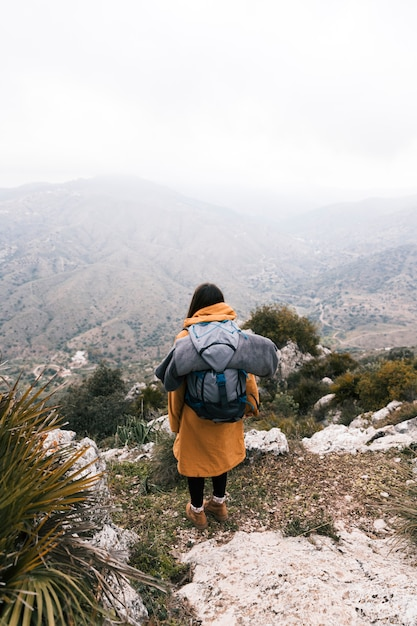 Una vista desde arriba de una mujer joven con su mochila con vistas a la montaña Foto gratis