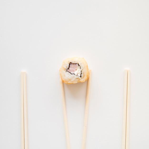 Vista desde arriba palillos sosteniendo un rollo de sushi Foto gratis