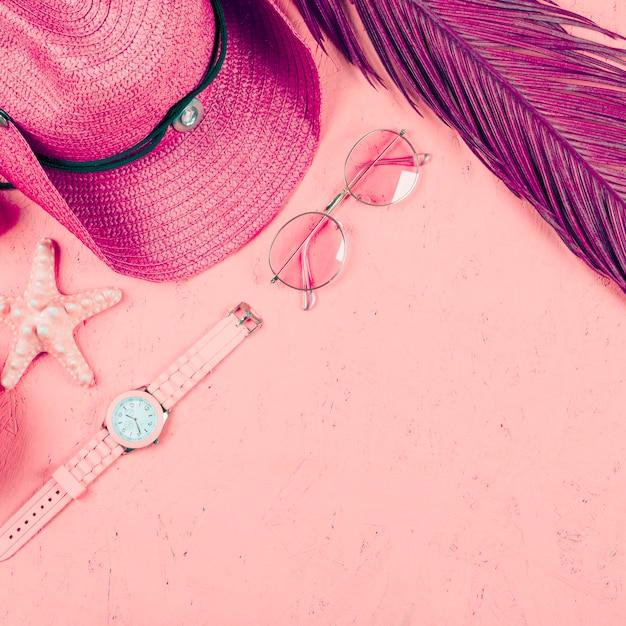 Una vista desde arriba del reloj de pulsera; gafas de sol; sombrero; hoja y estrellas de mar sobre fondo rosa con textura Foto gratis