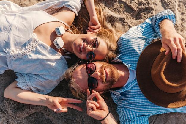 Vista desde arriba sobre el joven sonriente feliz hombre y mujer en gafas de sol tumbado en la playa de arena Foto gratis