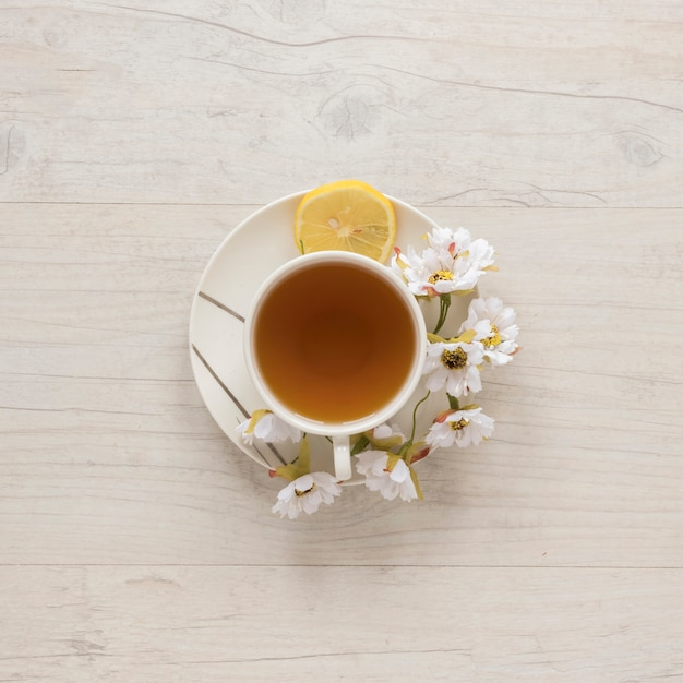 Vista de arriba del té del limón en taza con las flores y el limón en el platillo Foto gratis