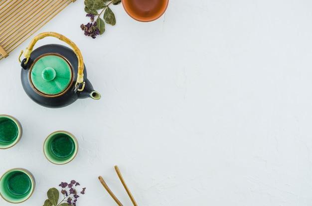 Una vista de arriba de la tetera y de las tazas herbarias verdes de cerámica con las hierbas aisladas en el fondo blanco Foto gratis