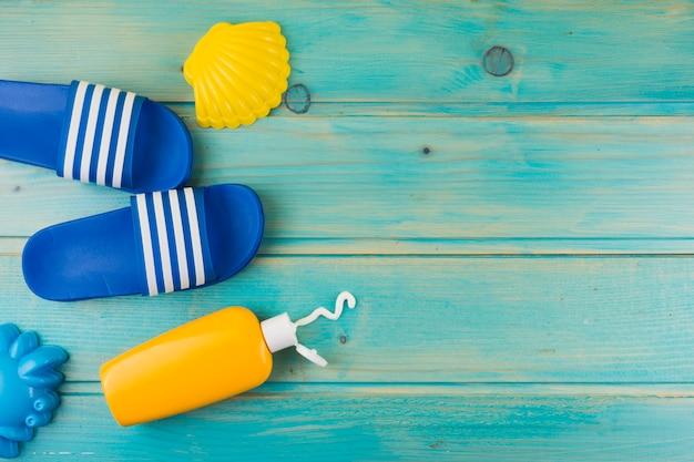 Una vista desde arriba de la vieira de plástico amarillo; chanclas y botella de loción de protección solar sobre fondo de madera turquesa Foto gratis