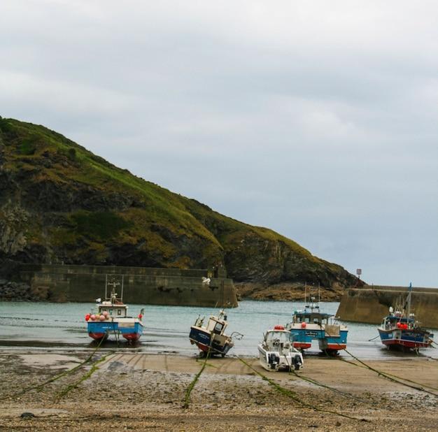 Vista de barcos en una playa de arena con una montaña y un cielo nublado Foto gratis