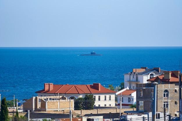 Una vista de las casas en construcción, el cielo y un submarino en el mar. Foto Premium