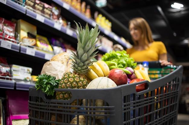 Vista de cerca del carro de la compra sobrecargado con comida mientras que en el fondo la persona femenina elige productos Foto gratis