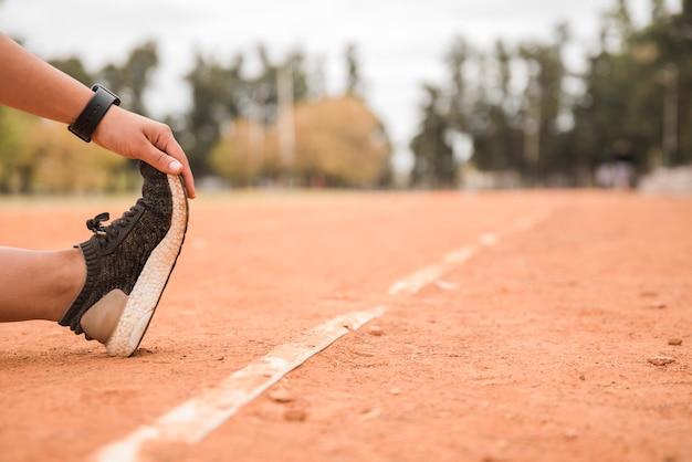Vista de cerca de mujer deportiva estirando en pista de estadio Foto gratis