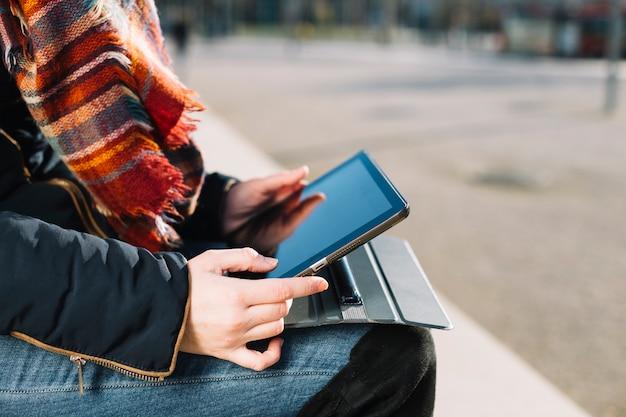 Vista de cerca de mujer de negocios trabajando al aire libre con tableta Foto gratis