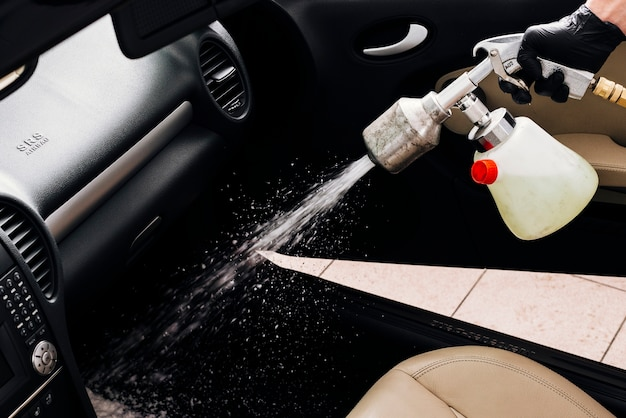 Vista de cerca de persona limpiando interior de coche Foto gratis