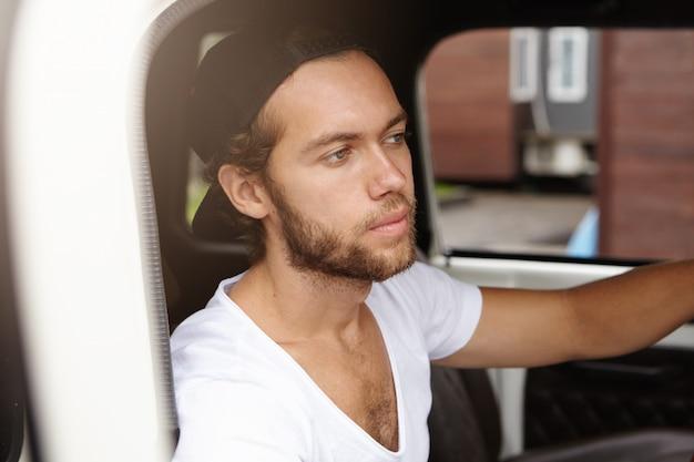 Vista cercana de atractivo joven barbudo en snapback sentado dentro de la cabina de su jeep blanco Foto gratis