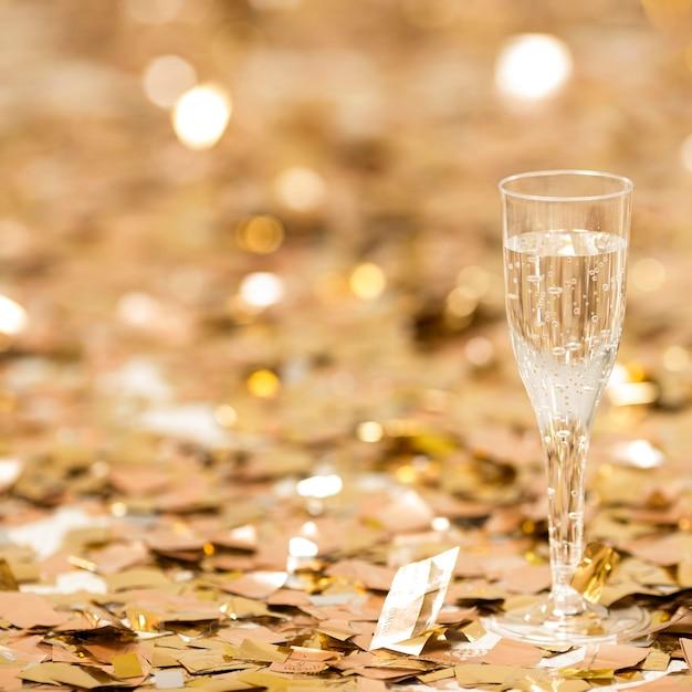 Vista cercana de copa de champán con confeti Foto gratis