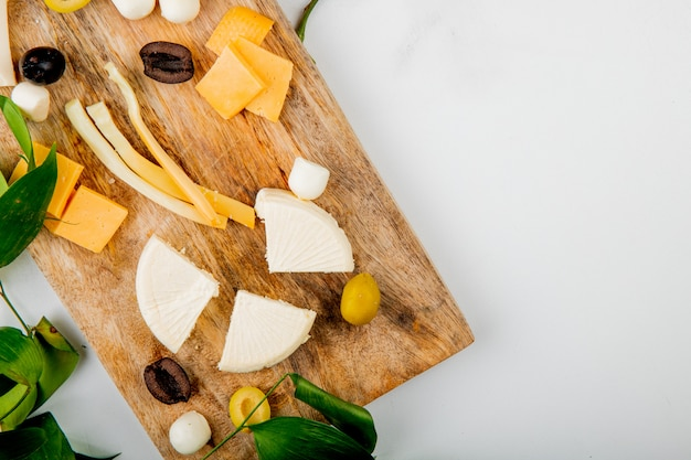Vista cercana de diferentes tipos de queso con trozos de uva aceitunas en tabla de cortar en blanco decorado con flores y hojas con espacio de copia Foto gratis