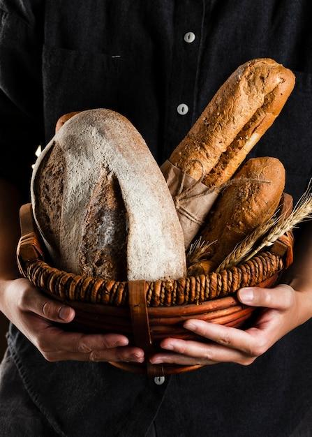 Vista cercana de un hombre sosteniendo una cesta de pan Foto gratis