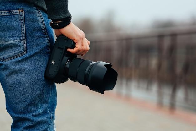 Vista cercana de la mano masculina que sostiene la cámara profesional en la calle. Foto gratis