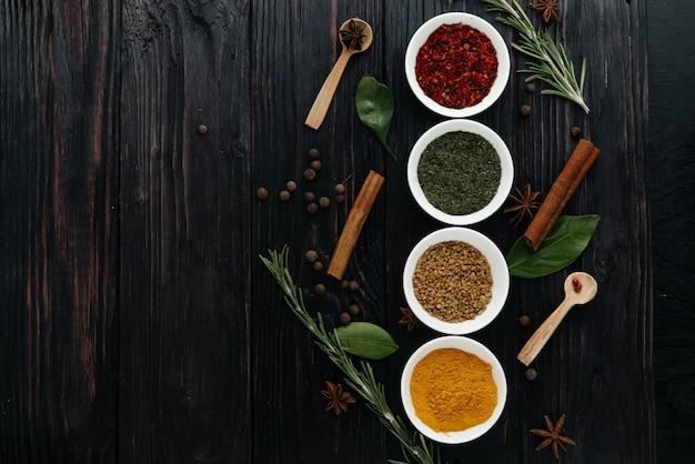 La vista desde la cima. cocina india. condimento. condimentos con hierbas frescas y secas en tazones. espacio libre para copiar Foto Premium