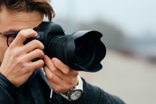 Vista detallada de hombre joven en lentes tomando fotos en la calle.