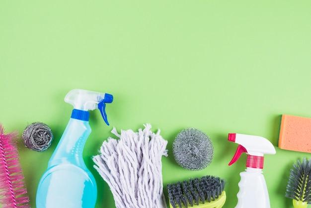 Vista elevada de artículos de limpieza en el contexto verde Foto gratis