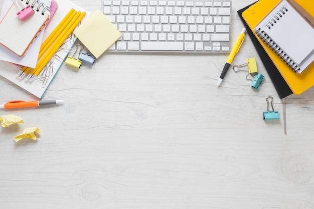 Una vista elevada de los artículos de papelería de oficina con teclado y espacio para copiar el texto en el escritorio de madera Foto gratis