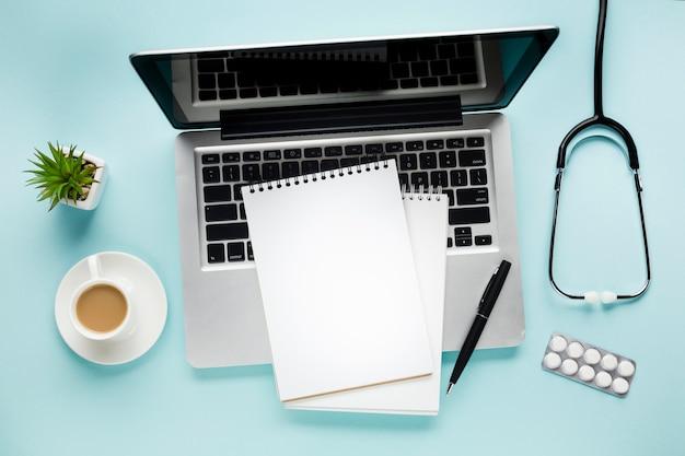 Vista elevada del bloc de notas en la computadora portátil cerca de la taza de café y la planta suculenta sobre el escritorio médico Foto gratis