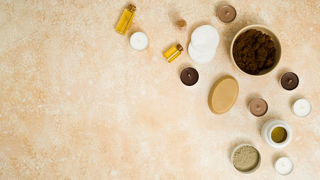 Una vista elevada de café en polvo; jabón de hierbas; velas; bastoncillos de algodón; aceite esencial y polvo de arcilla rhassoul sobre fondo texturado beige Foto gratis