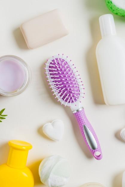 Una vista elevada del cepillo para el cabello con productos cosméticos contra el fondo blanco Foto gratis