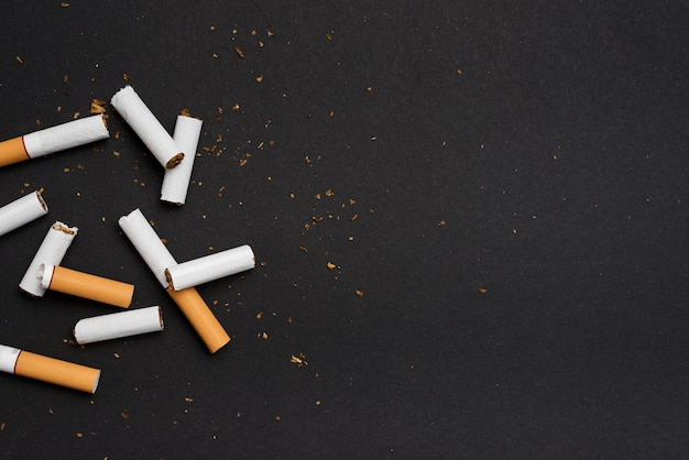 Vista elevada de cigarrillo roto sobre fondo negro Foto gratis